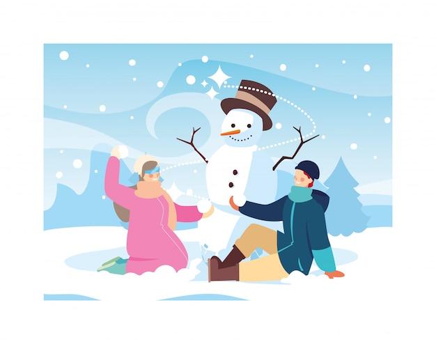 Couple de personnes avec bonhomme de neige dans le paysage d'hiver