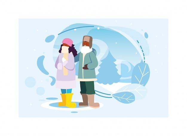 Couple de personnes avec des vêtements d'hiver dans le paysage avec des chutes de neige