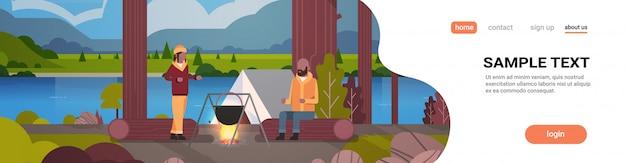 Couple, randonneurs, cuisine, repas, dans, melon, ébullition, pot, à, feu camp, près, camp, tente, camping, concept, paysage, nature, rivière, montagnes, fond, horizontal, pleine longueur, copie, espace