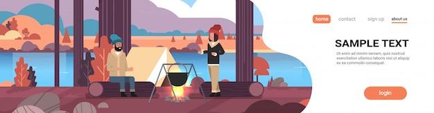 Couple, randonneurs, femme homme, cuisine, repas, dans, melon, ébullition, pot, à, feu camp, près, camp, tente, camping, automne, paysage, nature, rivière, montagnes