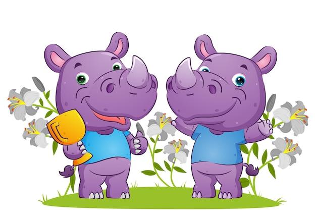 Le couple de rhinocéros gagnant célébrant la victoire en tenant l'illustration du trophée