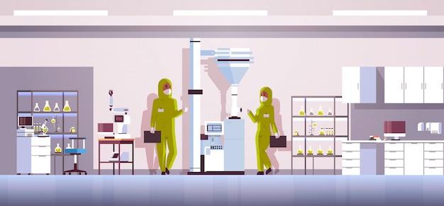 Couple de scientifiques travaillant avec panneau de commande en appuyant sur le bouton de démarrage sur une machine spéciale