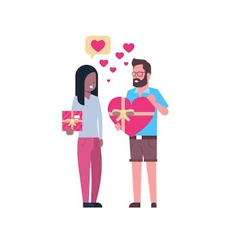 Couple tenant des coffrets cadeaux en forme de coeur isolé valentin concept de vacances