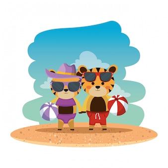 Couple de tigres avec chapeau d'été et ballons sur la plage