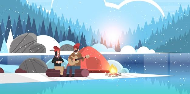 Couple, touristes, randonneurs, délassant, dans, camp, homme, jouer guitare, pour, petite amie, séance, sur, bûche, randonnée, concept, lever soleil, paysage hiver, nature, rivière, forêt, montagnes