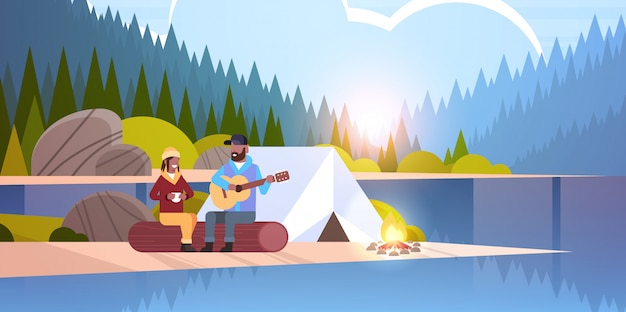 Couple, touristes, randonneurs, délassant, dans, camp, homme, jouer guitare, pour, petite amie, séance, sur, journal randonnée, concept, lever soleil, paysage, nature, rivière, forêt, montagnes, fond, horizontal