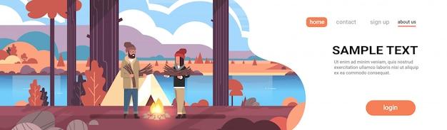Couple, touristes, randonneurs, tenue, bois chauffage, homme, femme, organisation, feu, près, camp, tente, randonnée, camping, automne, paysage, nature, rivière, montagnes
