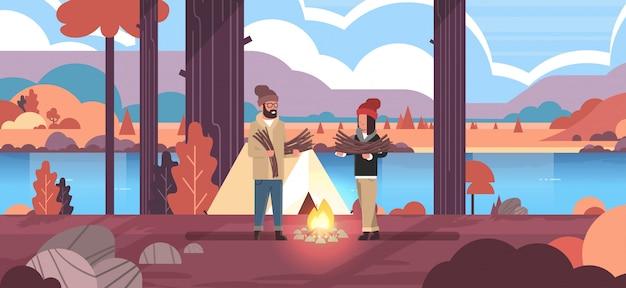 Couple, touristes, randonneurs, tenue, bois chauffage, homme, femme, organisation, feu, près, camp, tente, randonnée, camping, concept, automne, paysage, nature, rivière, montagnes