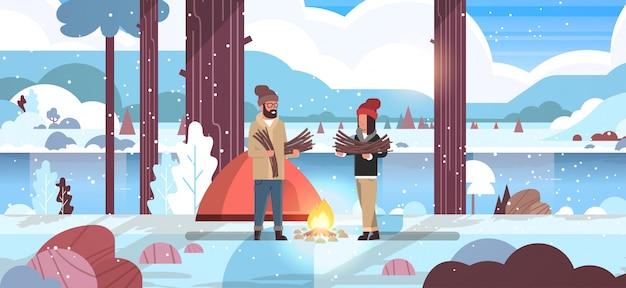 Couple, touristes, randonneurs, tenue, bois chauffage, homme femme, organisation, feu, près, camp, tente, randonnée, camping, concept, hiver, paysage, nature, rivière
