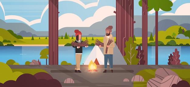 Couple, touristes, randonneurs, tenue, bois chauffage, homme, femme, organisation, feu, près, camp, tente, randonnée, camping, concept, paysage, nature, rivière, montagnes