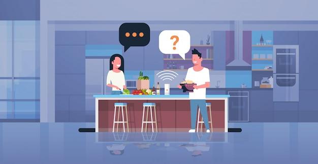 Couple, utilisation, intelligent, orateur, homme, femme, préparer, nourriture, demander, recette, reconnaissance vocale, concept, cuisine moderne, intérieur, plat, horizontal, pleine longueur