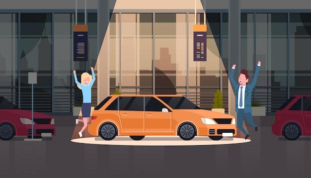 Couple de vendeur présentant une voiture neuve dans la salle d'exposition du centre du concessionnaire sur un ensemble de véhicules neufs