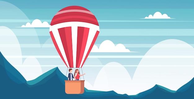 Couple, voler, dans, panier, de, montgolfière, homme, prendre photo, sur, appareil-photo smartphone, femme, pointage main, à, quelque chose, voyage, concept, montagnes, paysage, fond, horizontal