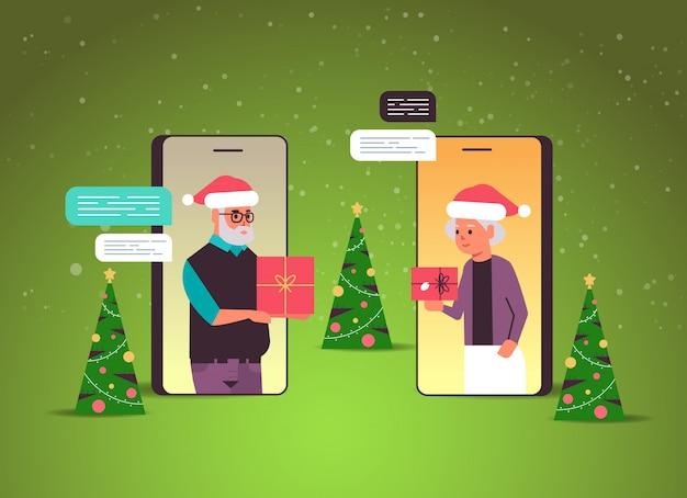 Couples aînés, dans, chapeaux santa, utilisation, chat, application, réseau social, chat, bulle, communication, concept