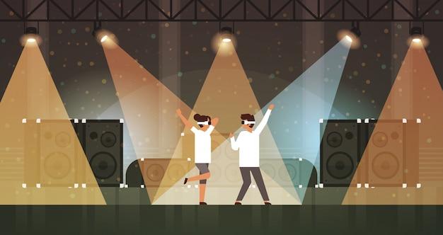 Couples de danseurs portant des lunettes de réalité virtuelle dansant sur scène avec effets de lumière disco studio équipements musicaux haut-parleur multimédia