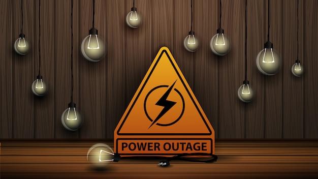 Coupure de courant, logo d'avertissement jaune sur l'arrière-plan du mur en bois et des ampoules ternes