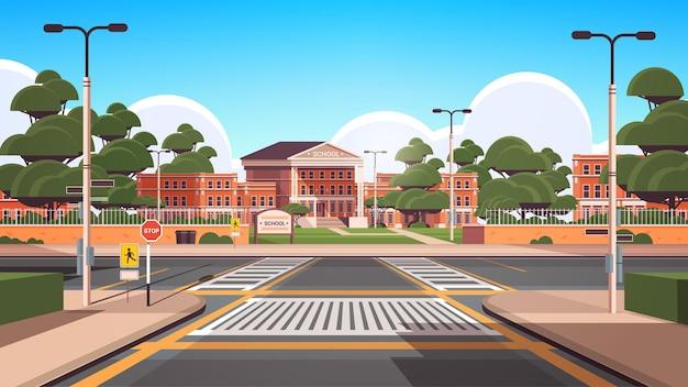Cour avant vide de bâtiment d'école avec le fond de paysage urbain d'été de concordance de route d'arbres verts