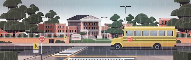 Cour avant vide de bâtiment d'école avec le passage pour piétons de route d'arbres et l'arrière-plan de paysage urbain d'autobus scolaire