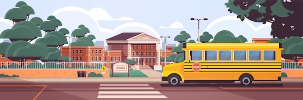 Cour avant vide de bâtiment d'école avec le passage pour piétons de route d'arbres verts et l'arrière-plan de paysage urbain d'été d'autobus scolaire