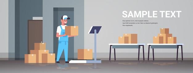 Courrier homme en uniforme mettant la boîte de colis sur des balances courrier express livraison concept de service logistique intérieur moderne entrepôt