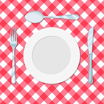 Couteau, cuillère et fourchette de plat sur une nappe rouge dans une cage