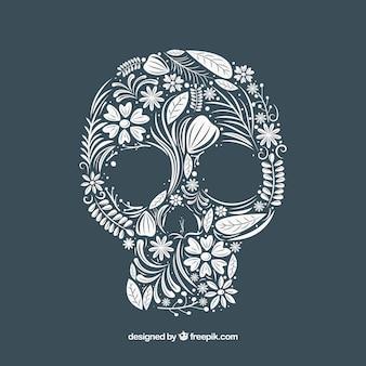 Crâne fond en main dessiné éléments floraux