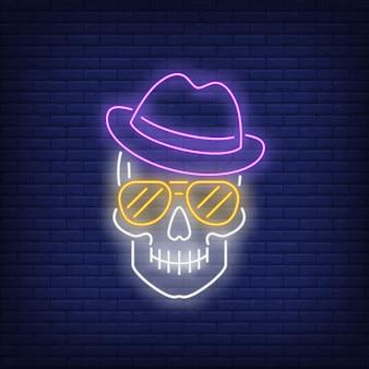 Crâne portant enseigne au néon de chapeau et lunettes de soleil