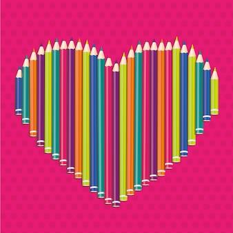 Crayons de couleur formant un coeur sur des points roses