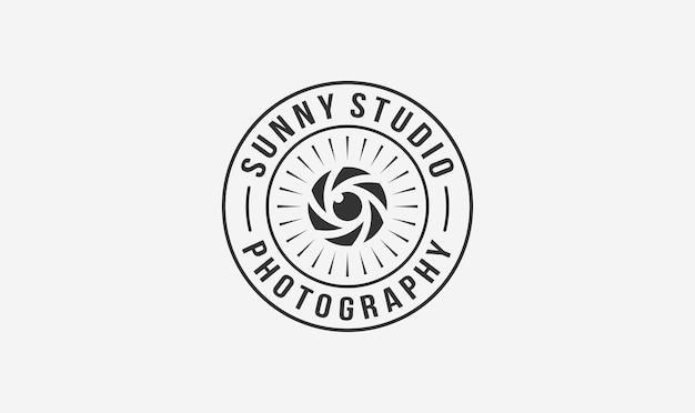 Création de logo de timbre de photographe de studio avec l'élément soleil et objectif.