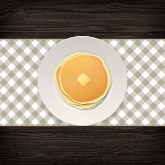 Crêpe réaliste avec un morceau de beurre sur une plaque blanche libre sur fond de bois, vue de dessus.