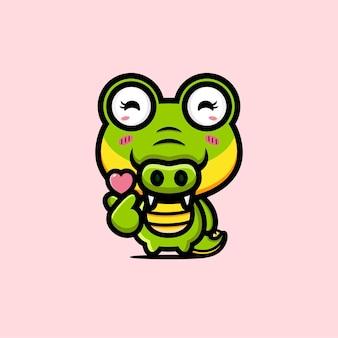 Crocodile mignon posant l'amour du doigt