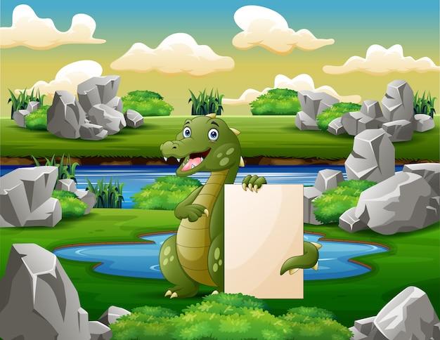 Un crocodile tenant une pancarte blanche près du petit étang