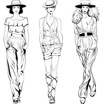Croquis noir et blanc des belles jeunes filles en tailleurs-pantalons et chapeaux isolés sur fond blanc