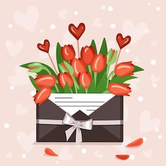 Décoration festive de la saint-valentin tulipes dans une enveloppe avec note d'amour et pendentifs coeurs