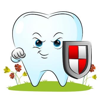 La dent tient le bouclier pour protéger le corps de l'illustration