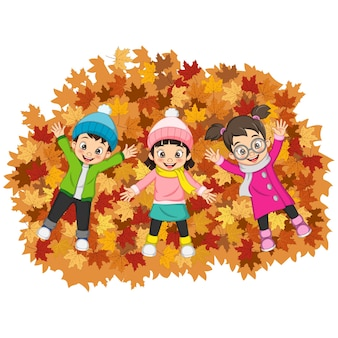 Dessin animé enfants heureux couché sur des feuilles d'automne colorées