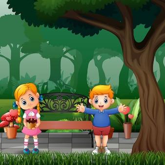 Dessin animé heureux garçon et fille tenant un petit gâteau