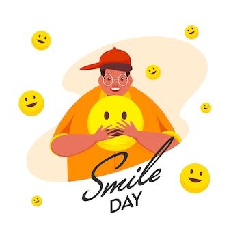 Dessin animé jeune homme tenant smiley emoji sur fond blanc pour le jour du sourire.