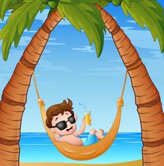 Dessin animé petit garçon relaxant sur la plage de hamac avec un cockta potable