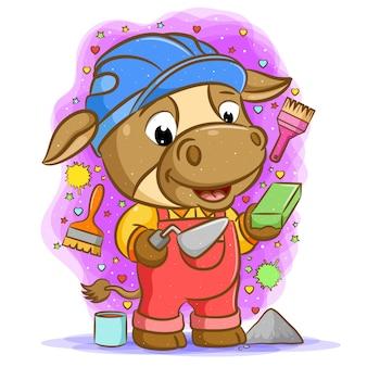Le dessin animé de la vache constructeur brun tenant une cuillère de ciment avec de la brique
