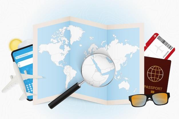 Destination de voyage érythrée, maquette de tourisme avec équipement de voyage et carte du monde avec loupe sur une érythrée.