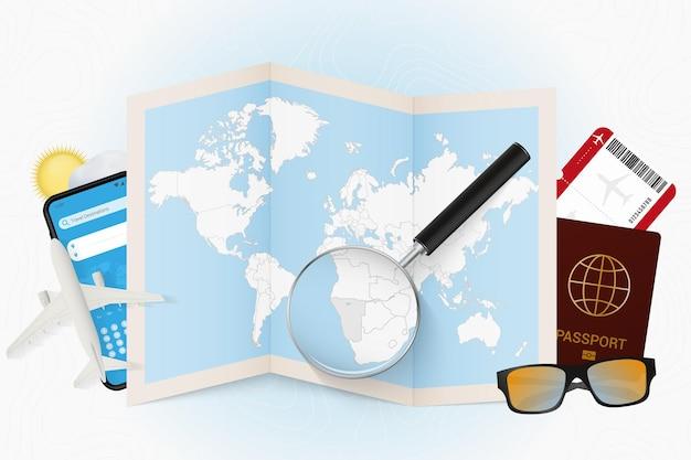 Destination de voyage namibie, maquette de tourisme avec équipement de voyage et carte du monde avec loupe sur une namibie.