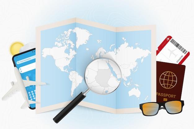 Destination de voyage soudan, maquette touristique avec équipement de voyage et carte du monde avec loupe sur un soudan.