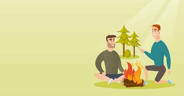 Deux amis assis autour d'un feu de joie dans le camping