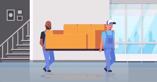 Deux courriers de course mixtes en uniforme canapé mobile concept de service de livraison express déménageurs de meubles professionnels tenant un nouveau canapé intérieur de salon moderne