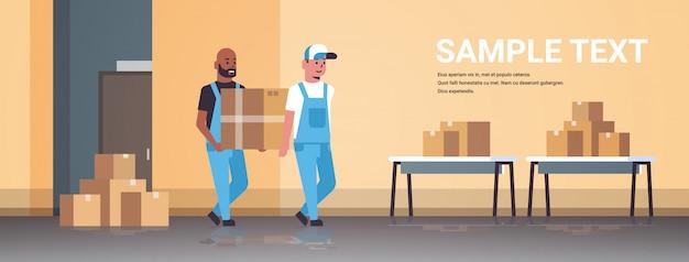 Deux coursiers en uniforme transportant la boîte en carton package mail express service de livraison concept mix race industrielle travailleurs d'usine travaillant dans l'entrepôt de l'entrepôt