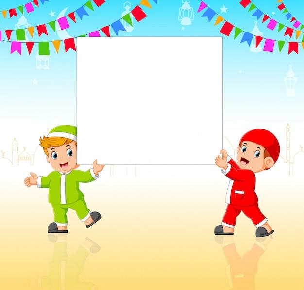 Deux enfants tiennent le tableau vide dans la soirée
