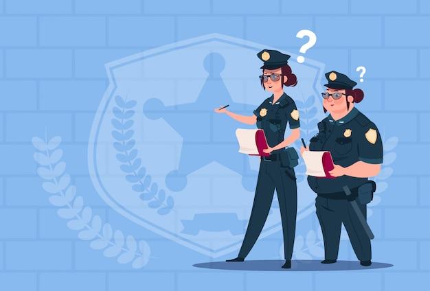 Deux femmes policiers détenant des boîtes avec des employés de bureau licenciés vêtus d'uniformes gardes féminins sur fond de briques bleues