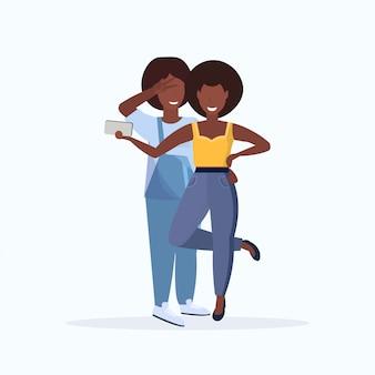 Deux femmes prenant une photo de selfie sur l'appareil photo du smartphone personnages de dessins animés féminins debout ensemble posant sur fond blanc pleine longueur