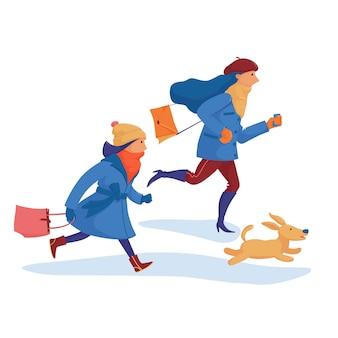 Deux filles, des amis dans des vêtements chauds et un chien se dépêchant de faire du shopping, ayant peur de manquer les réductions, se précipitant, courant vite